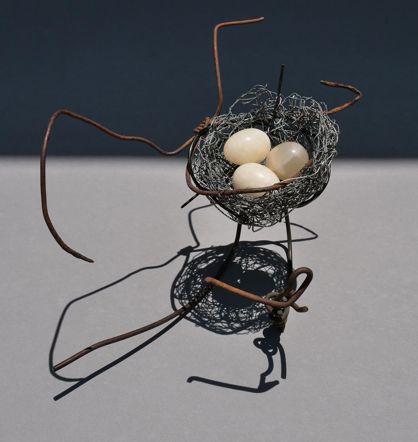 Nest 2. Handmade wire nest approximately 25 cm wide and 17 cm high with polished stone eggs 3 cm.