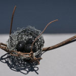 Nest 4. Handmade wire nest approximately 26 cm wide and 10 cm high with polished stone eggs 3 cm.